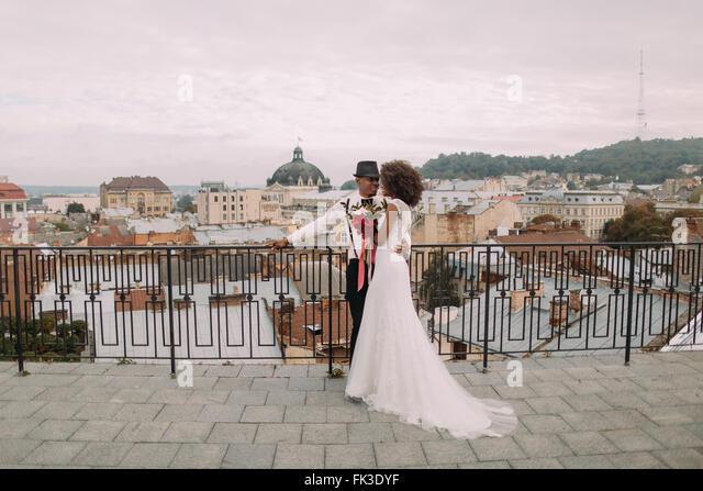 Glücklich schwarz Hochzeitspaar sanft umarmt auf dem Dach Stockbild