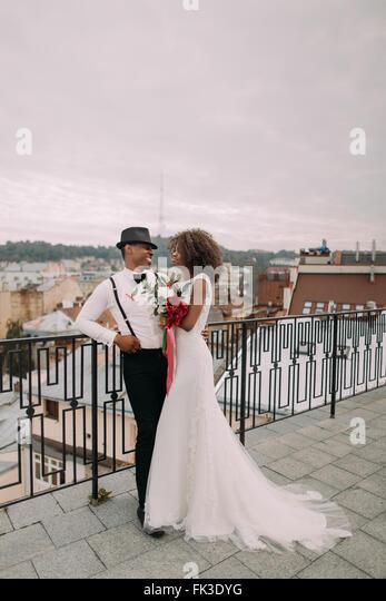 Schöne afrikanische Hochzeitspaar schauen liebevoll einander auf dem Dach Stockbild