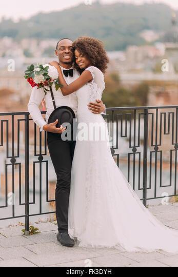 Glücklich schwarze Braut und Bräutigam umarmt sanft auf der Terrasse mit Stadtbild auf Hintergrund Stockbild
