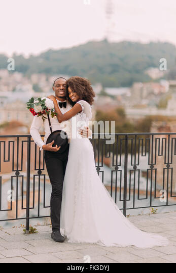 Schöne afrikanische Hochzeitspaar stehen auf dem Balkon am Tag ihrer Hochzeit Stockbild