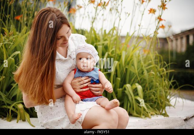 Niedliche glücklich Kleinkind auf liebevolle Mutter Knien sitzen und Lächeln auf den Lippen. Familienspaß. Stockbild