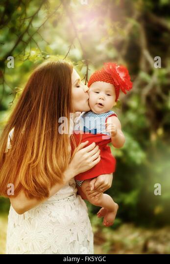 Porträt der jungen Mutter Holding zu lieben und zu küssen ihr Baby. Sonnenlicht, selektiven Fokus. Stockbild