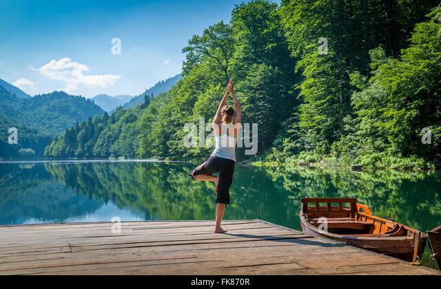 Yoga-Übungen am Berg Wald See. Stockbild