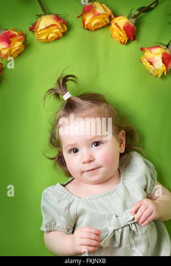 hübsches kleines Mädchen mit gelben Rosen auf grüne Decke liegend Stockbild