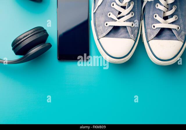 Kopfhörer, Smartphone und Sneakers auf farbigen Hintergrund Stockbild