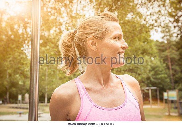 Reife Frau mit Pferdeschwanz im Park tragen Weste suchen Sie lächelnd Stockbild