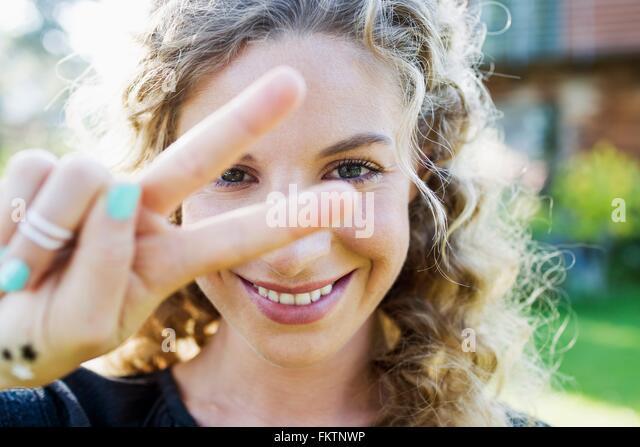 Junge Frau, die Peace-Zeichen mit der Hand machen - Stock-Bilder