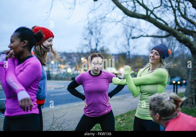 Fünf Erwachsenen Läuferinnen Aufwärmen am Rande der Stadt in der Abenddämmerung Stockbild