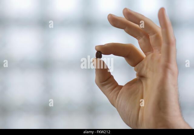 Finger halten C Gebühr Bohne Stockbild