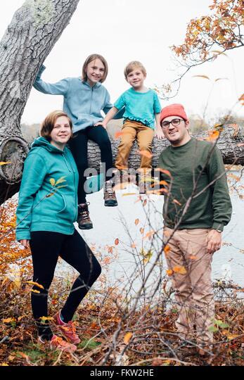 Porträt der Familie, Kinder sitzen auf Baum Stockbild