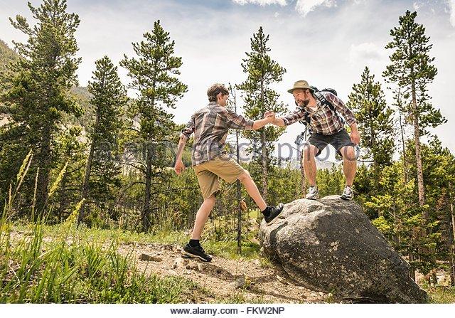 Vater im Wald, Händchenhalten Sohn, helfen sich an Felsen, Red Lodge, Montana, USA - Stock-Bilder
