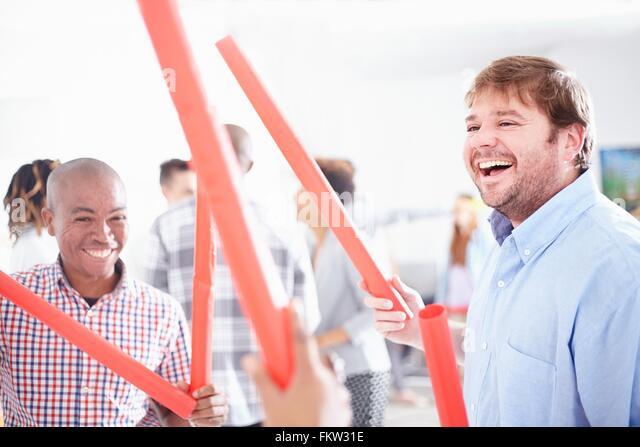 Kolleginnen und Kollegen im Team-building Aufgabe halten rote Röhren lächelnd Stockbild