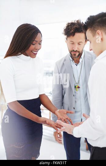 Kolleginnen und Kollegen im Team-building Aufgabe von Angesicht zu Angesicht Händchenhalten blickte lächelnd Stockbild