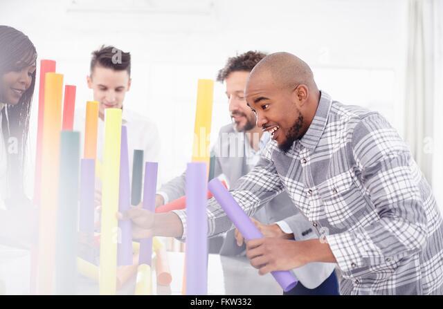 Kolleginnen und Kollegen im Team-building Aufgabe Ausgleich bunten Röhren lächelnd Stockbild