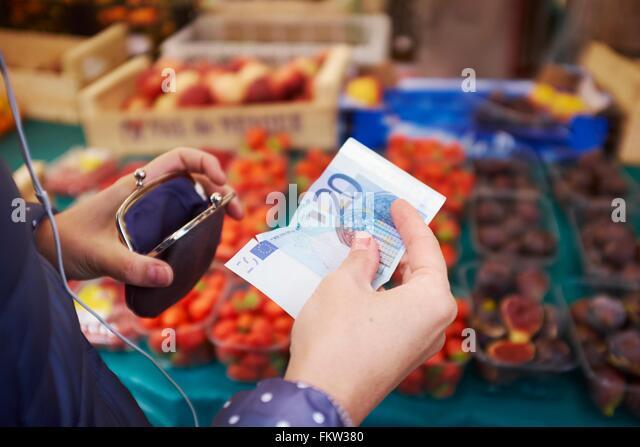 Junge Frau am Markt, wobei Geld vom Geldbeutel, Mittelteil Stockbild