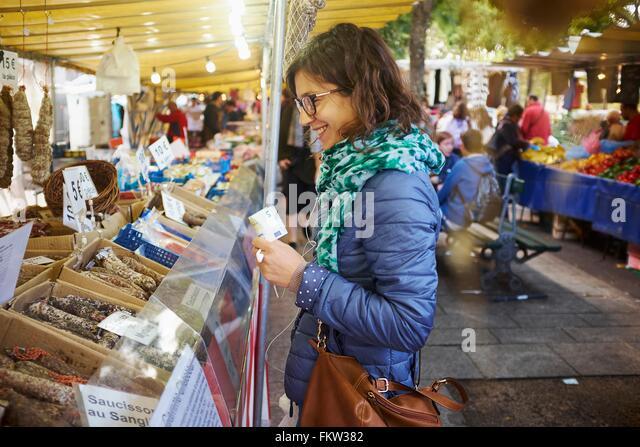Junge Frau, die frische Lebensmittel am Marktstand kaufen Stockbild
