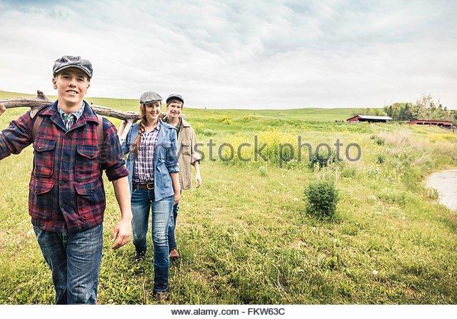 Junge Erwachsene und teenboy tragen Zweig auf Schulter Blick auf die Kamera zu Lächeln Stockbild