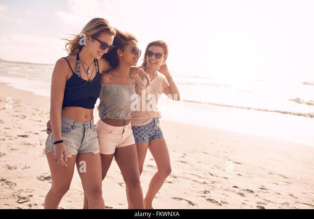 Porträt von drei jungen Freundinnen zu Fuß am Ufer Meeres. Gemischtrassig junge Frauen, die an einem Sommertag - Stock-Bilder