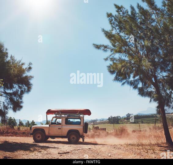Seitenansicht des Kajak beladen SUV auf der Landstraße. Fahren auf Land an einem sonnigen Tag. Stockbild