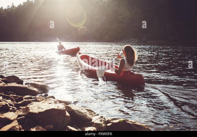 Junge Menschen in einem See paddeln. Junger Mann und Frau Kajaks paddeln, an einem sonnigen Tag. Stockbild