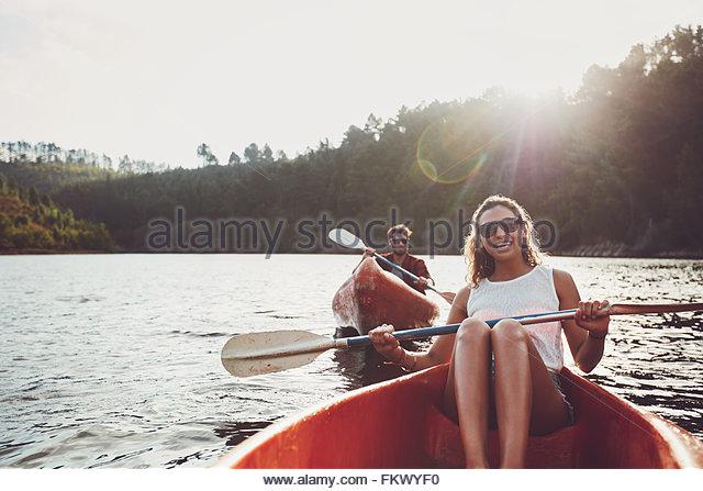 Glückliche junge Frau mit ihrem Freund Rudern auf der Rückseite in einem See paddeln. Glückliches Stockbild