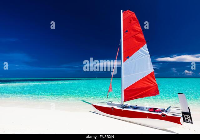 Segelboot mit roten Segel auf den Strand der einsamen tropischen Insel mit blauen Flachwasser Stockbild