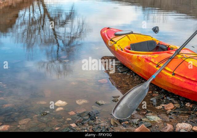 bunte Fluss Kajak mit einem Paddel auf felsigen Seeufer mit einer Baum-Reflexion - Erholung-Konzept Stockbild
