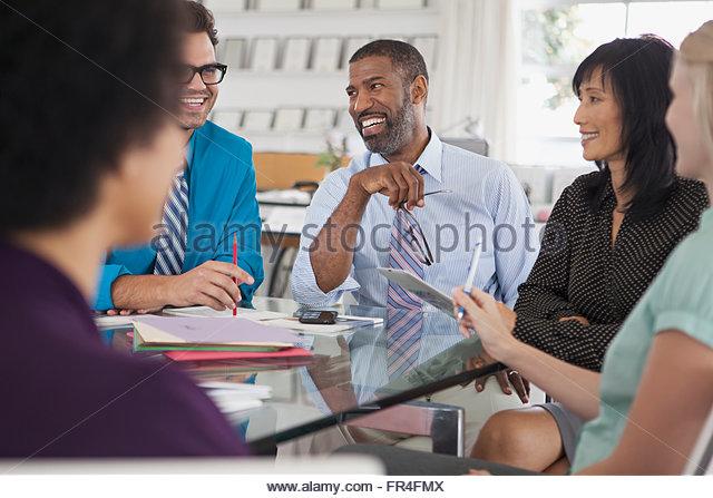 fünf Geschäftsleute mit einem Lachen während der Sitzung Stockbild