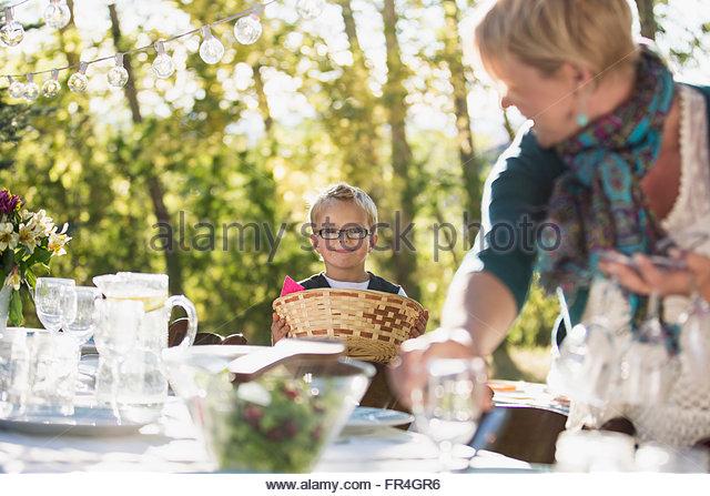 Sechs Jahre alter Junge seiner Mutter, legen Sie einen Tisch im Freien zu helfen. Stockbild