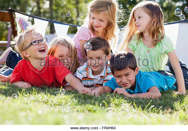 Cousins und Cousinen Bläschen zu fangen, da sie auf dem Rasen liegen. Stockbild