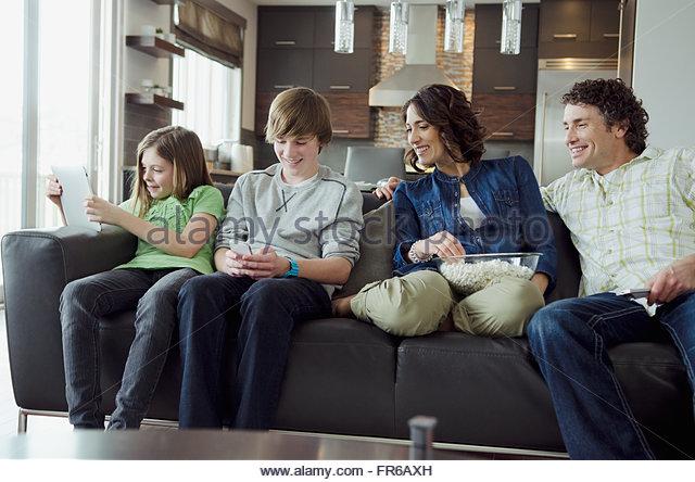 Familie auf Sofa mit Technik beschäftigt Stockbild