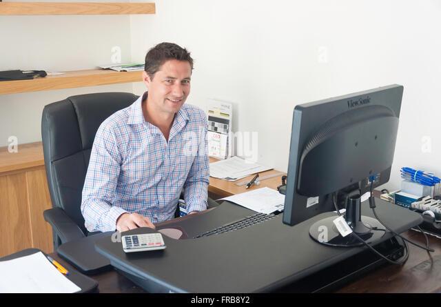 Junge executive männlich (30) im Büro Schreibtisch, Christchurch, Provinz von Canterbury, Neuseeland Stockbild