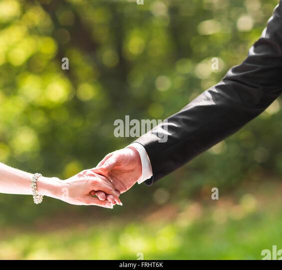 Glückliches Paar Hand in Hand im freien Stockbild
