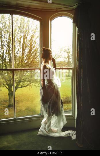 junge Frauen stehen am Fenster Stockbild
