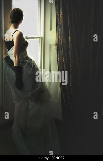 junge elegante Frau am Fenster im Altbau Stockbild