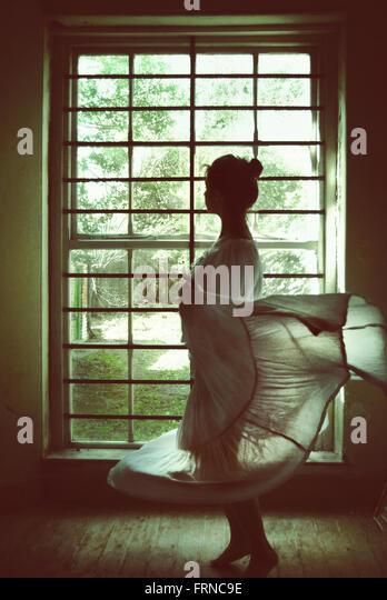junge Frau in ein altes Haus Zimmer mit einem großen Fenster tanzen Stockbild