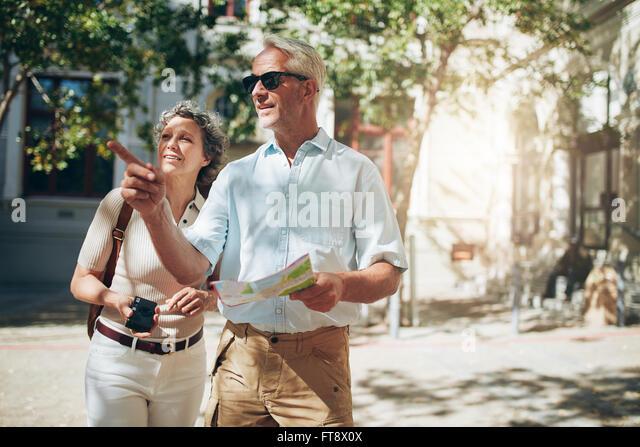 Älteres paar Touristen eine fremde Stadt zu erkunden. Älteres Paar mit Karte und auf der Suche nach der Stockbild