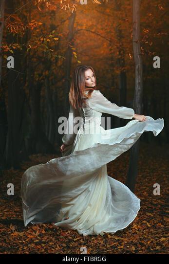 Schöne Frau im dunklen herbstlichen Wälder tanzen. Surreal und Fantasie Stockbild