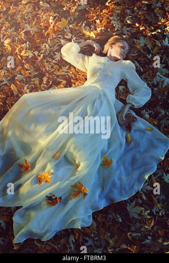 Schöne Frau mit viktorianischen Kleid auf einem Bett aus Blättern. Trauer und Einsamkeit-Konzept Stockbild