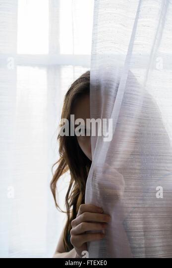 Ernste junge Frau versteckt sich hinter die Vorhänge am Fenster Stockbild
