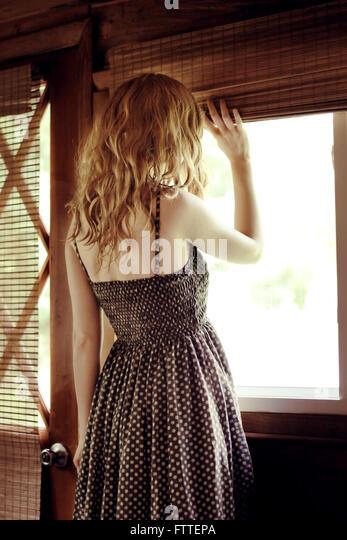 Frau am Fenster Stockbild