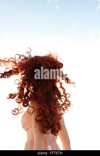 Lockige rothaarige Frau drehen Stockbild