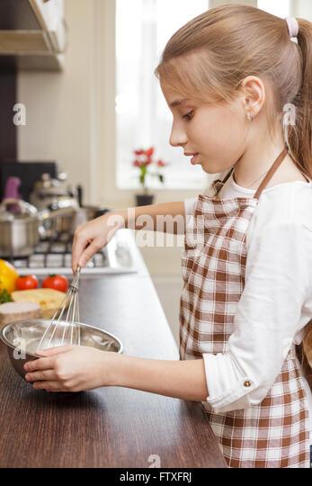Kleinen Mädchens in Schürze schlagen von Eiern in weiße Schüssel in der Küche Stockbild
