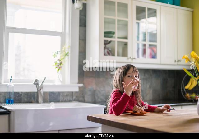 Mädchen sitzen in der Küche essen Schokolade Dessert und Finger lecken Stockbild