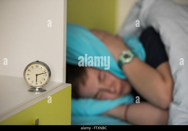 Junge im Bett für seine Ohren beim Wecker klingeln Stockbild