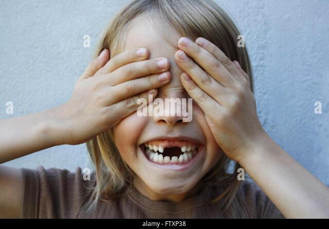 Junge mit Lücke gezahnten Lächeln mit Händen, Augen bedecken Stockbild