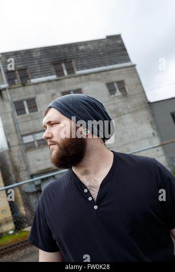 Junger Erwachsener Mann im Freien in einem städtischen Umfeld für Lifestyle Portrait eines bärtigen Stockbild