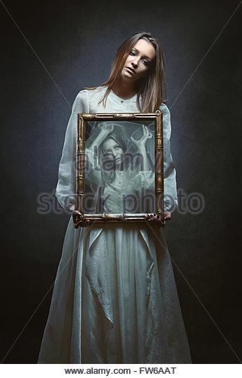 Seele einer schönen Frau in einem Spiegel gefangen. Dark Fantasy und surreal Stockbild