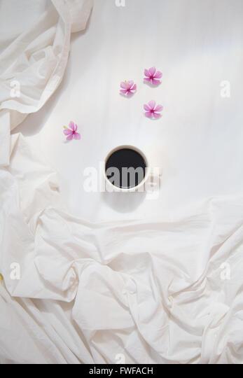Weiße Tasse schwarzen Kaffee auf weiße Bettwäsche mit rosa Blüten Stockbild