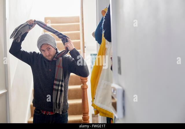Ein Mann in einen Wintermantel, Mütze und Schal Zuhause angekommen, seinen Schal auszuziehen. Stockbild